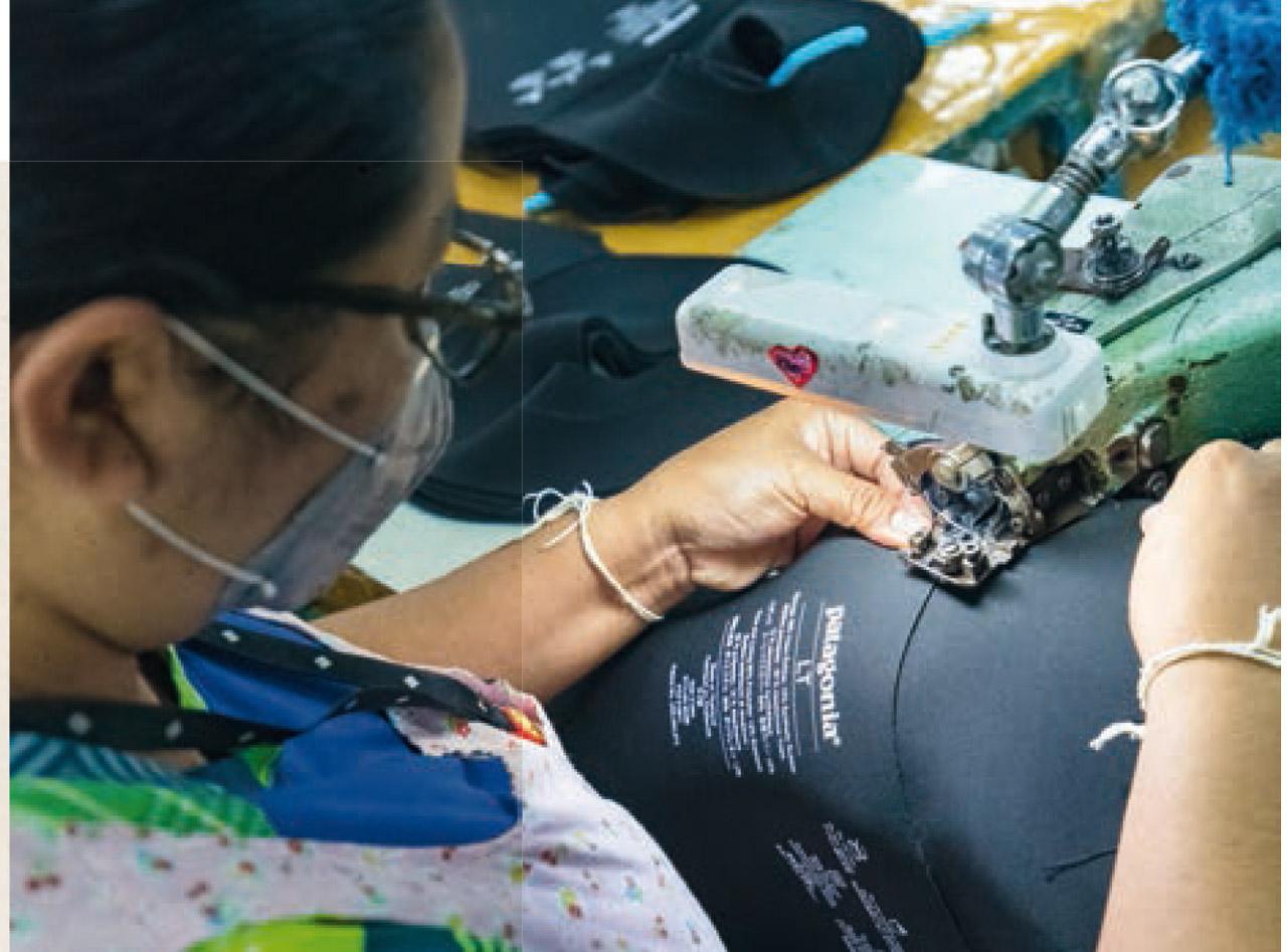 Eines der großen Anliegen von Patagonia sind sozial verträglichere Arbeitsbedingungen an den Produktionsstätten. Eine Näherin beim Zusammennähen eines Wetsuits ohne Neopren |©Patagonia